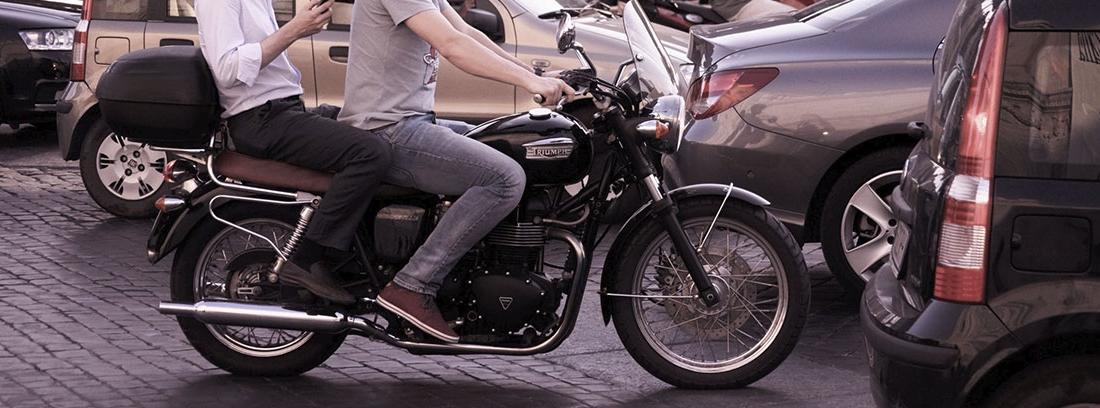 Moto negra con dos personas sobre ella con casco negro entre otros vehículos