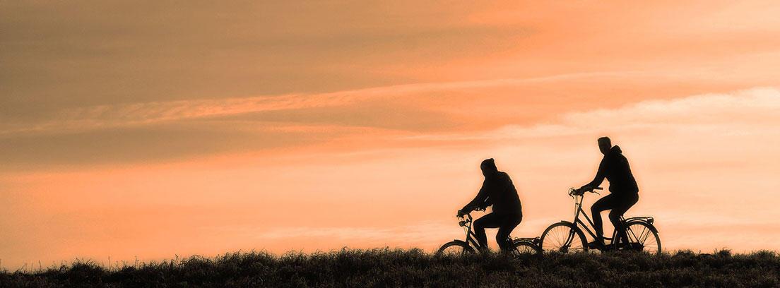 Dos personas pedaleando al atardecer
