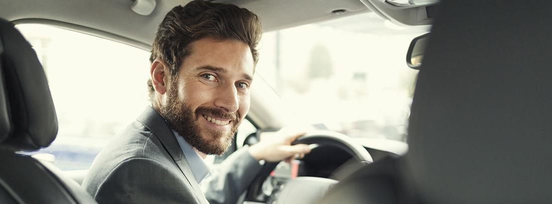 Hombre con barba y traje posa para una foto dentro del vehículo