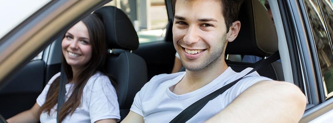 Hombre joven sonríe sentado al volante de un vehículo al lado mujer joven.