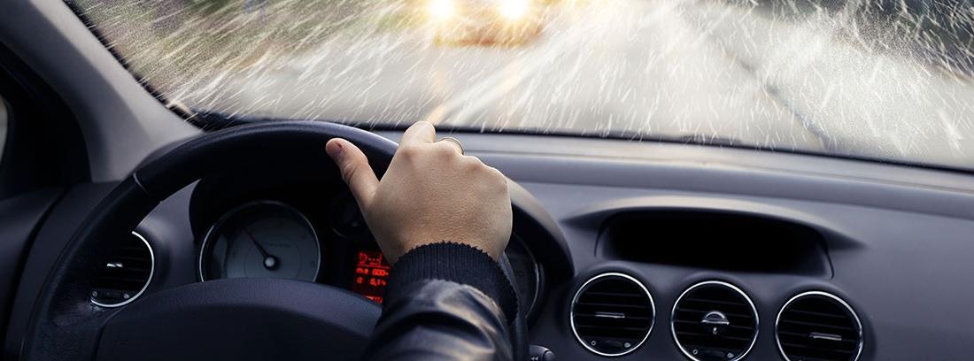 Interior de un coche conduciendo bajo la lluvia