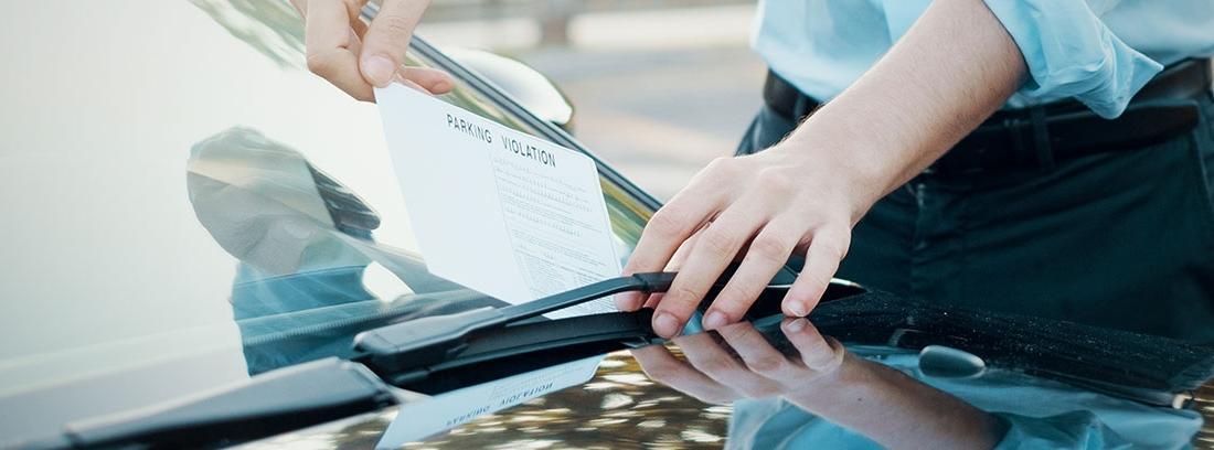 Agente poniendo una multa en un coche