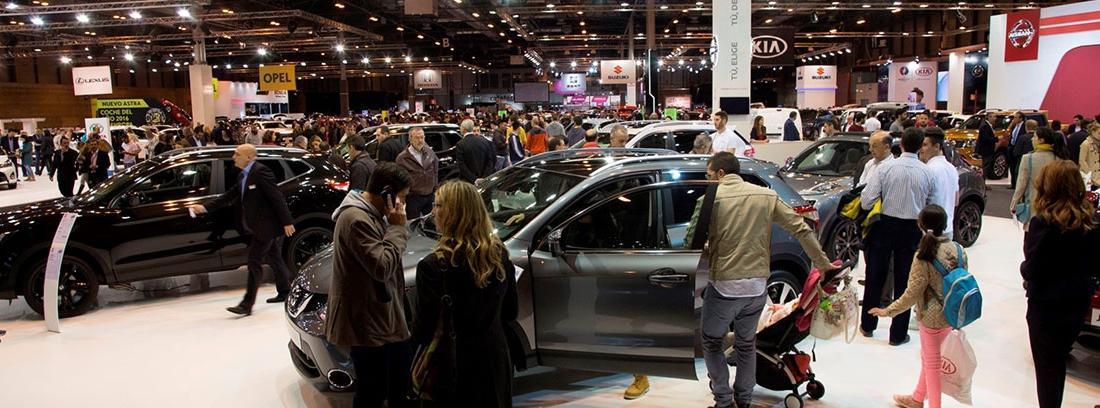 Vista general de pabellón con coches, carteles y personas.