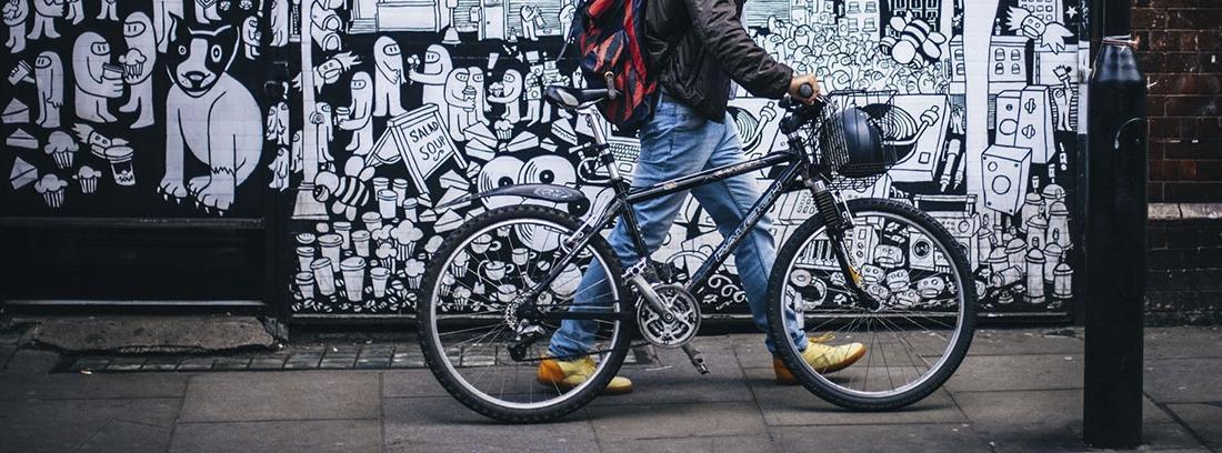 Hombre con mochila y móvil anda sujetando una bici a su lado.