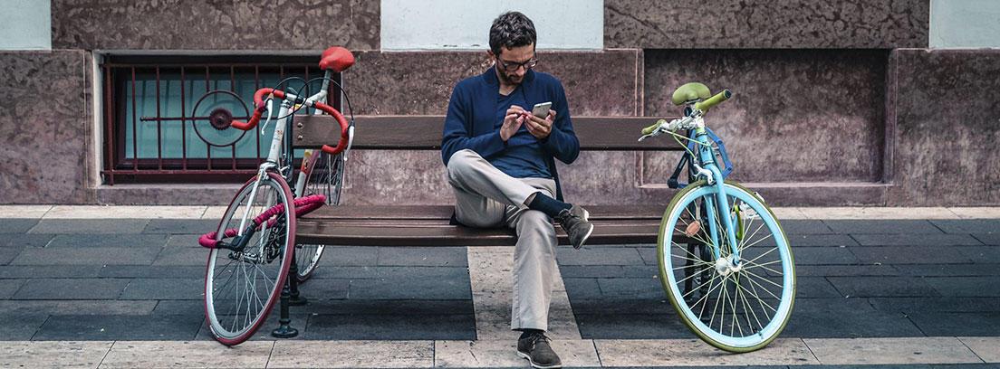 Hombre con gafas mira móvil sentado en banco con dos bicicletas.