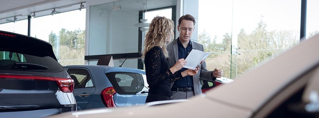 Mujer y hombre realizando una venta de un coche