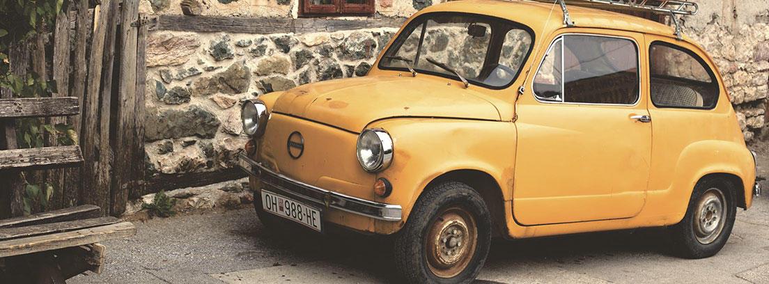Coche pequeño amarillo antiguo aparcado junto a pared de piedra