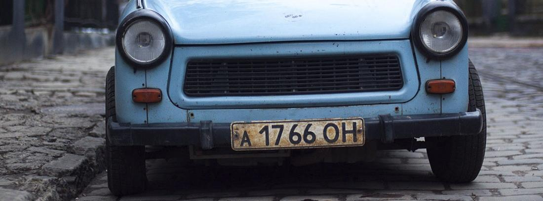 Coche pequeño y azul con matricula envejecida.