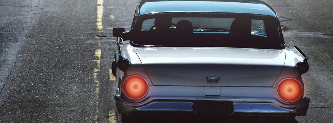 En carretera vista trasera de coche azul antiguo con farros rojos encendidos.