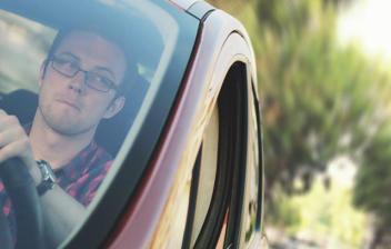 Hombre con gafas dentro e coche con una mano sobre volante