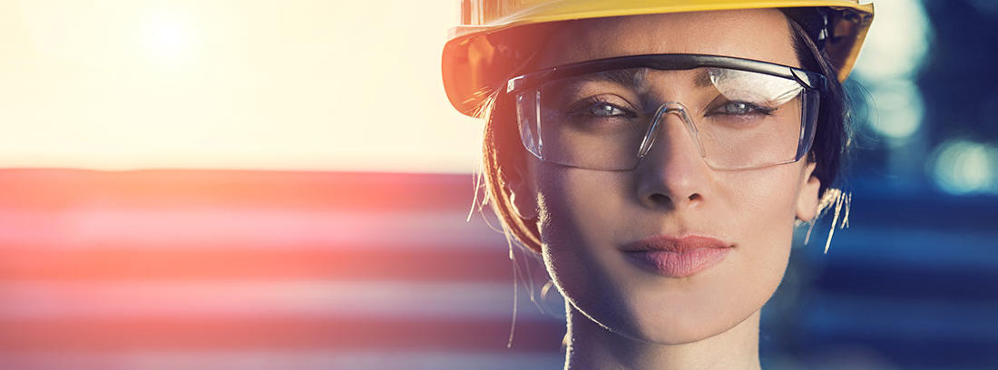 Mujer con casco amarillo y gafas protectoras