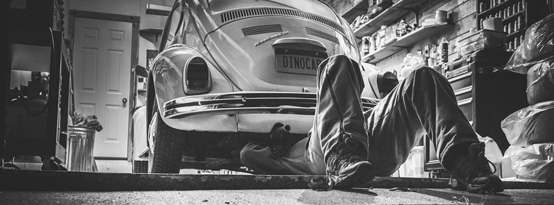 Persona arreglando la parte inferior de un coche antiguo en un almacén.