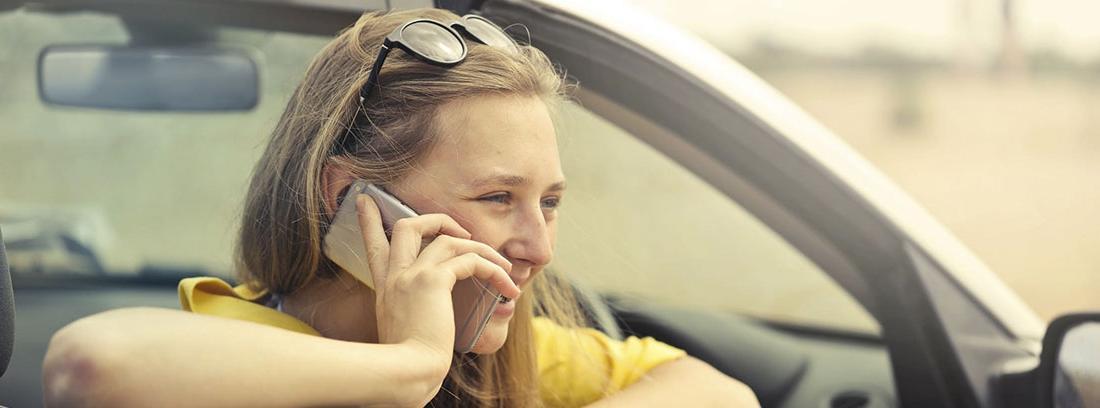 Mujer sentada dentro de coche y apoyada en ventana con teléfono sobre su oreja.