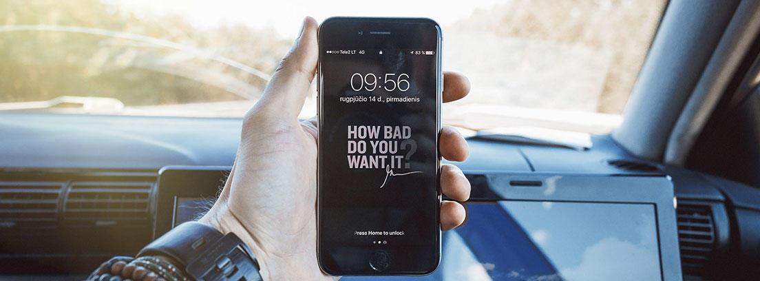 Mano sostiene un teléfono móvil dentro de un vehículo.