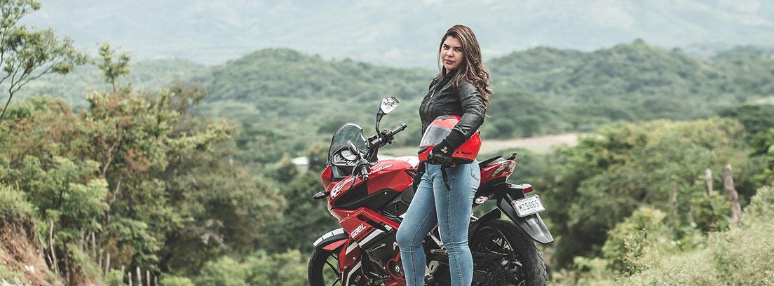 Mujer motorista posando con una motocicleta