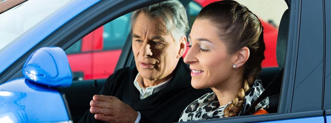 Profesor de autoescuela hace indicaciones a una conductora joven en un coche azul.