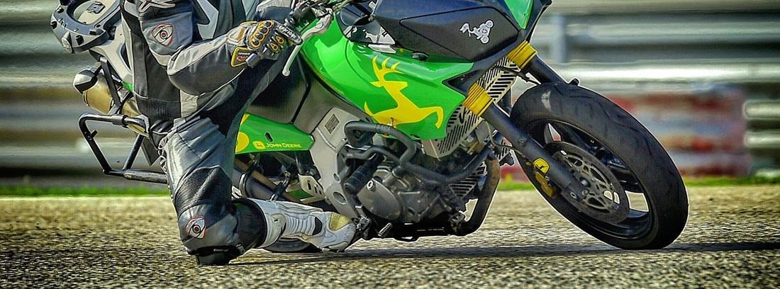 Motorista con casco sobre moto verde que inclina.