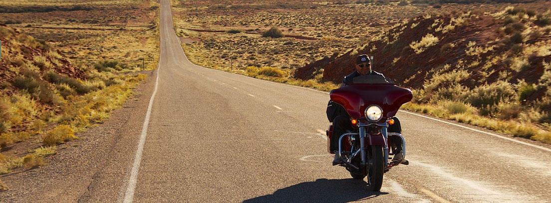 Hombre conduciendo moto por una larga carretera vacía.