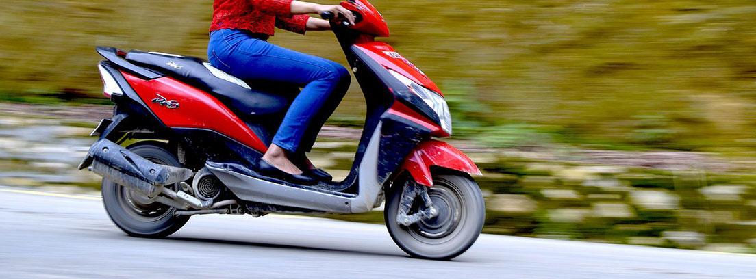 Mujer sobre moto scooter roja.
