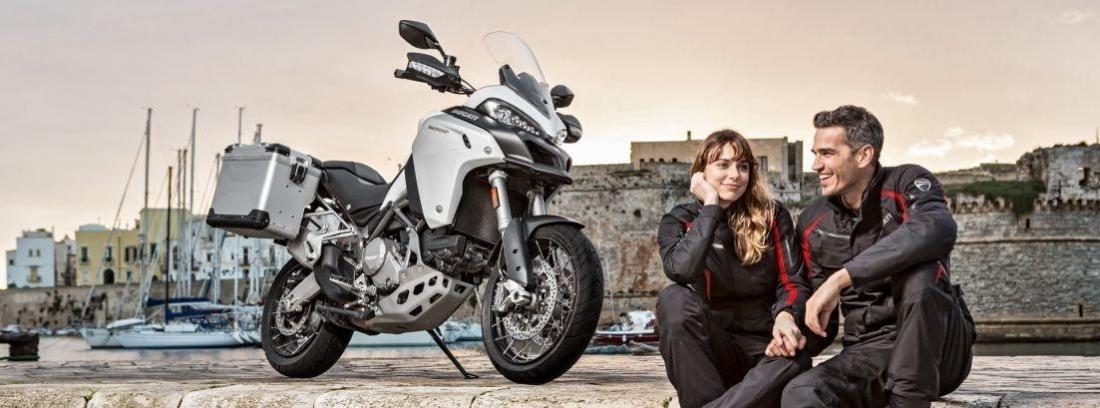 una pareja con su Ducati Multistrada 950 aparcada frente al mar