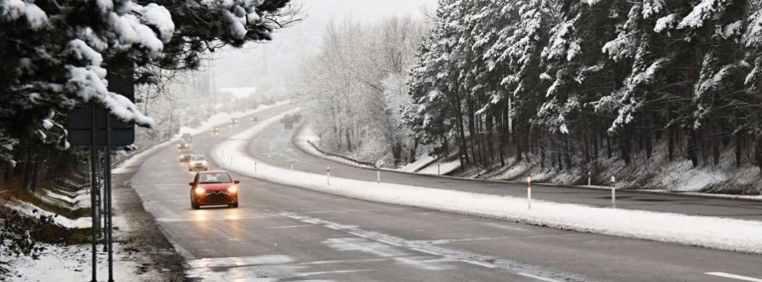 Coches circulando por carretera llena de nieve