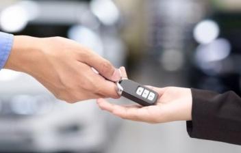 Manos sujetan llaves ante coches aparcados