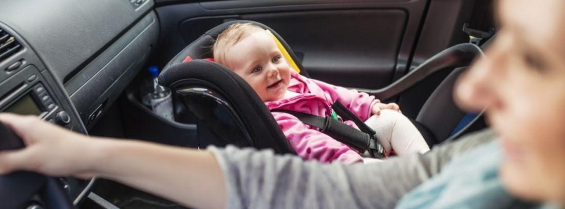 bebe en una sillita en el asiento delantero del coche