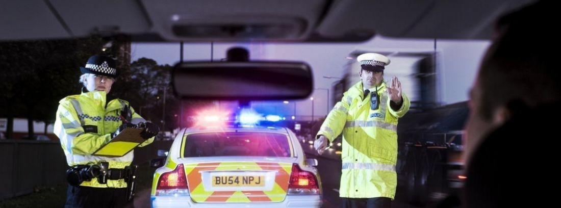 pareja de policias al lado de un coche patrulla con las luces encendidas