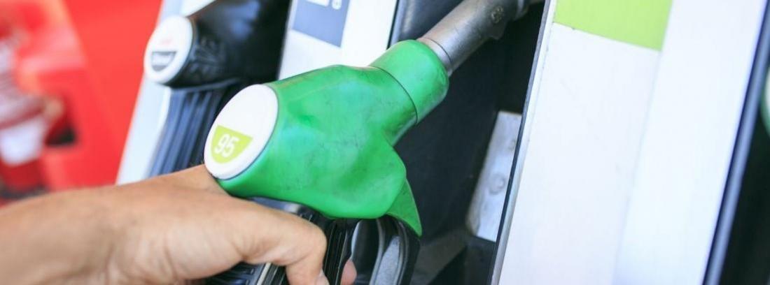 persona cogiendo un surtidor para echar gasolina