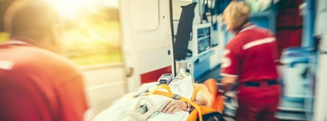Personal sanitario introduciendo a un hombre en una ambulancia