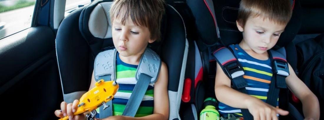 dos niños pequeños sentados en sillitas para niños en el coche