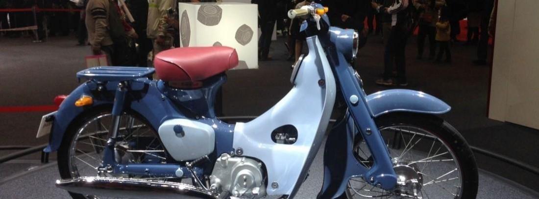 Imagen de la Honda Super Cub de color azul con sillín rojo