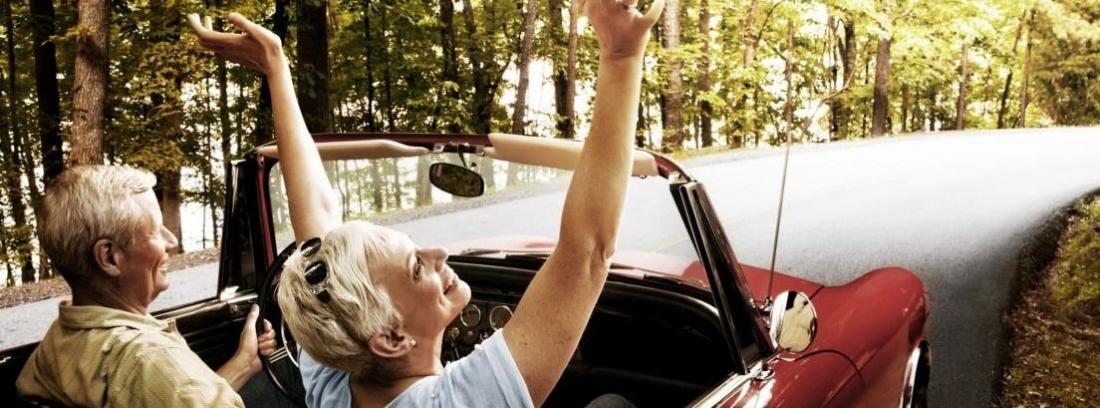 Dos personas mayores de espaldas con un coche descapotable