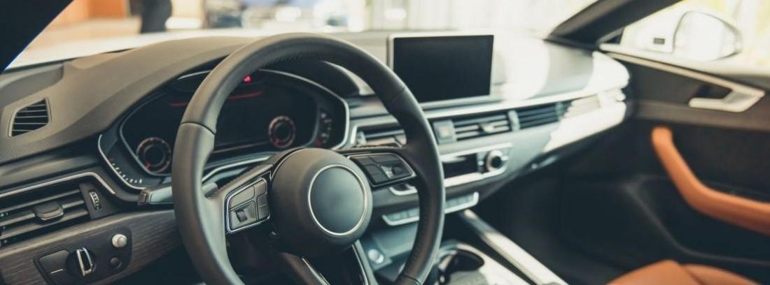 salpicadero de u coche con el volante en primer plano