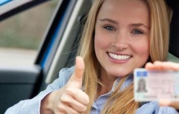 Adolescente posan sentado en su coche rojo enseña el permiso de conducción