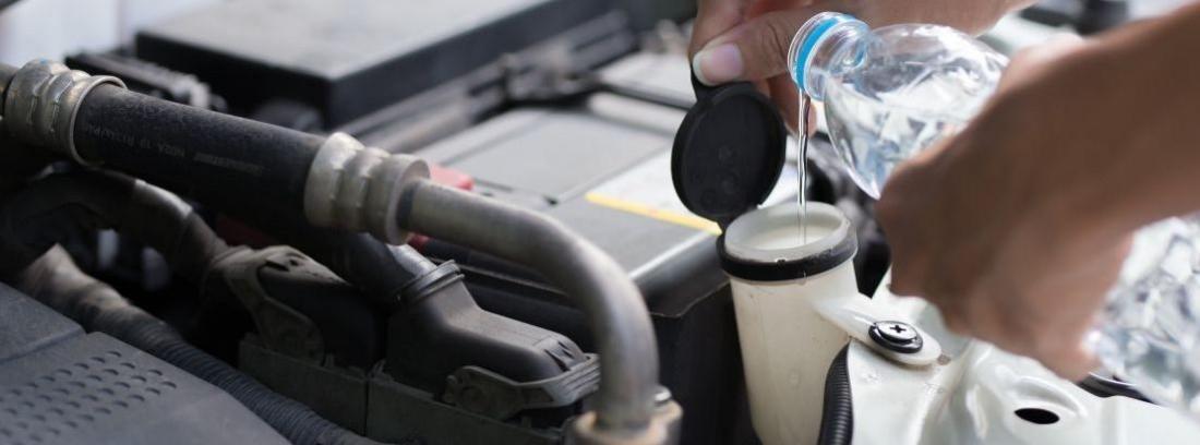 Mano con botella de agua rellenando liquido de un motor