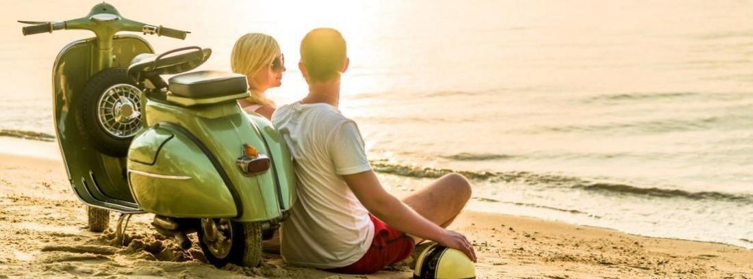 una pareja en la playa apoyada sobre una scooter tipo vespa
