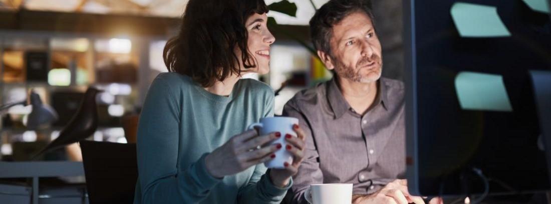 una pareja mirando a una pantalla de ordenador