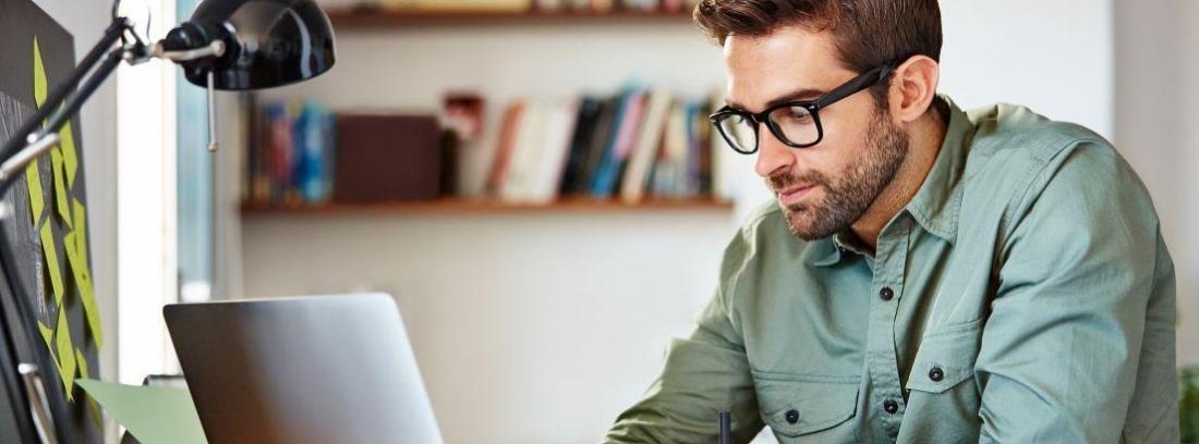 chico joven mirando la pantalla de un ordenador portátil