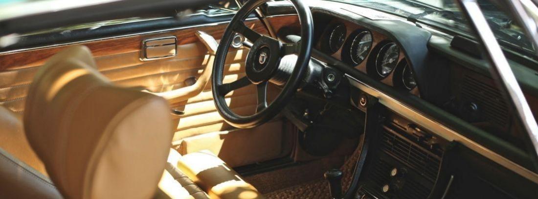 Diseño interior de coche con asientos de cuero y salpicadero de color madera.