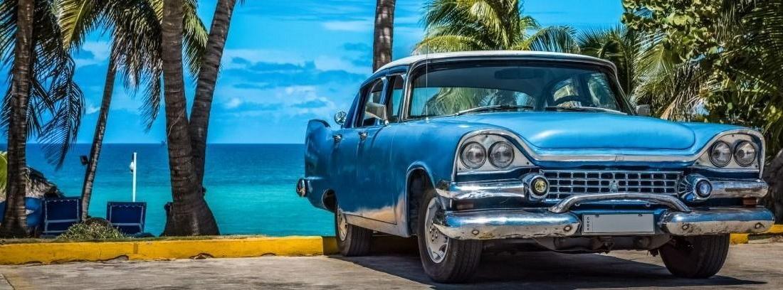 Coche histórico azul aparcado junto a una playa