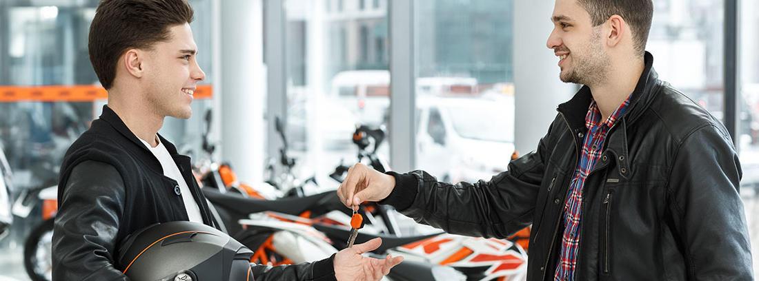Un vendedor entre las llaves de una moto nueva al comprador en un concesionario.