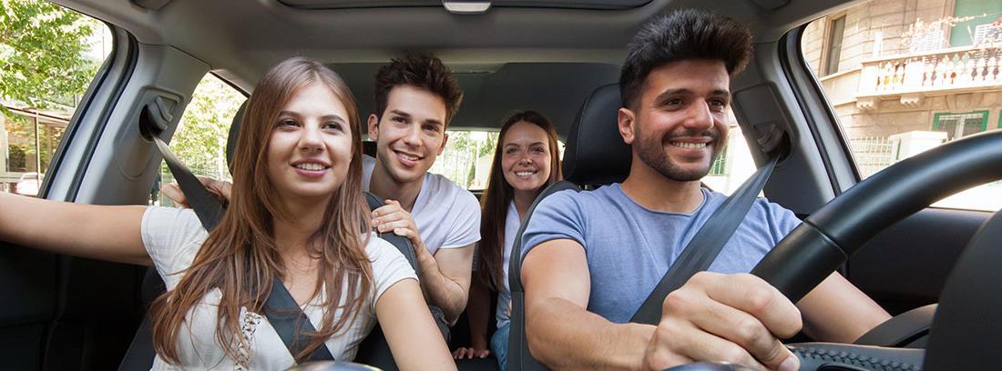 Cuatro jóvenes sonrientes en el interior de un coche