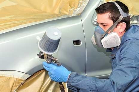 un hombre pintando un coche con spray en un taller