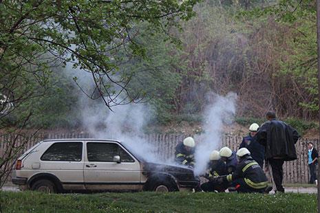 coche antiguo saliendo humo del capó y los bomberos apagando fuego