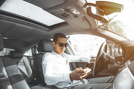 chico dentro del coche con gafas de sol mirando el smartphone