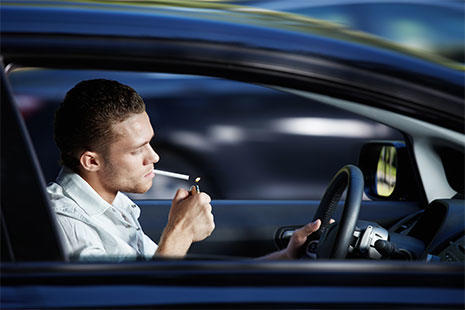 chico dentro del coche encendiendo un cigarro