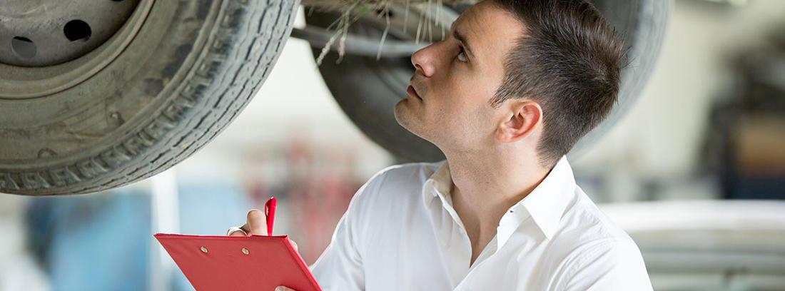 Hombre con bata blanca y libreta roja inspecciona un vehículo.