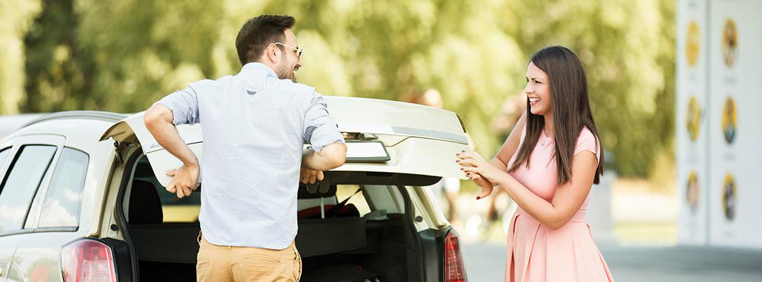 Hombre empujando puerta de maletero coche y mujer a su lado.