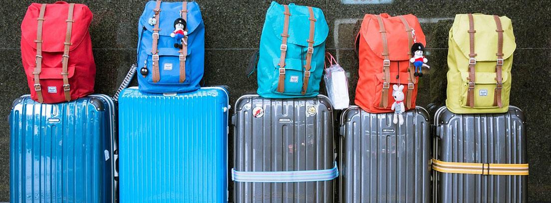 Fila de cinco maletas con ruedas con cinco mochilas sobre ellas.